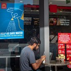 A man sits at an outdoor table at a McDonald's restaurant, next to a sign urging water conservation.