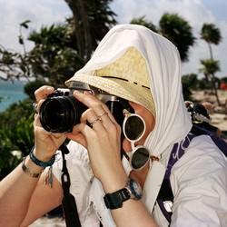 A tourist taking a photograph on a beach