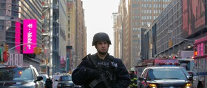 A photo of a police officer guarding the New York Port Authority Bus Terminal.