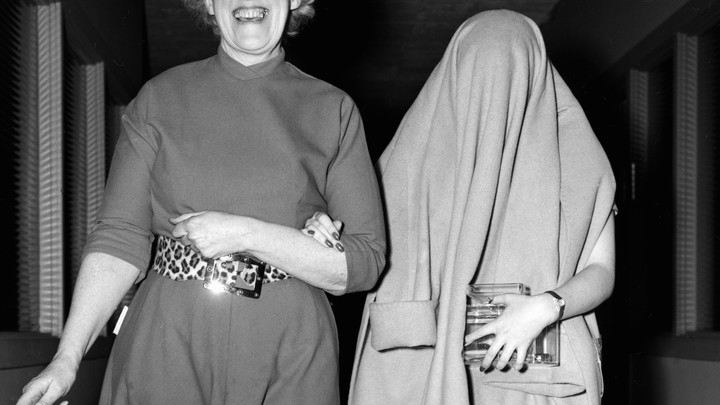 Black and white image of two women walking arm in arm, one with a big smile on her face, the other with a coat over her head, obscuring her face