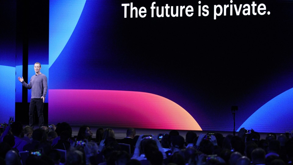 """Mark Zuckerberg speaks onstage in front of a sign that says """"The future is private."""""""