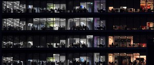 A view from outside a glass office tower at dusk of the workers inside.