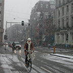 A woman rides her bike on a snowy day in Amsterdam.