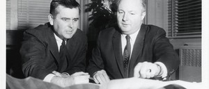 Two men look over city plans at a desk in an office.