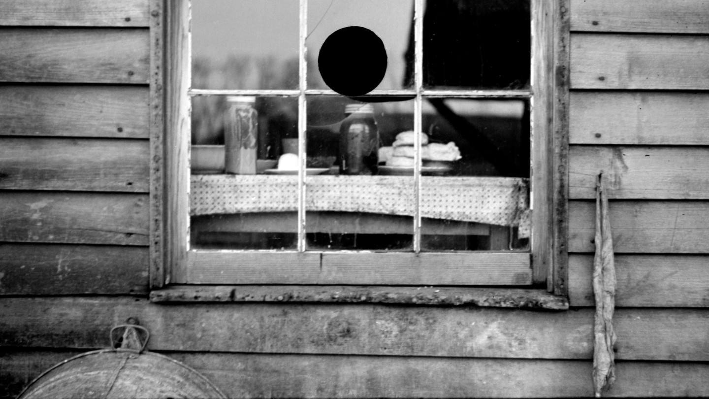 A black and white photo of a window in a wooden house, showing a table inside with jars on it