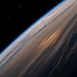 A view of the horizon and clouds at sunrise from Earth orbit