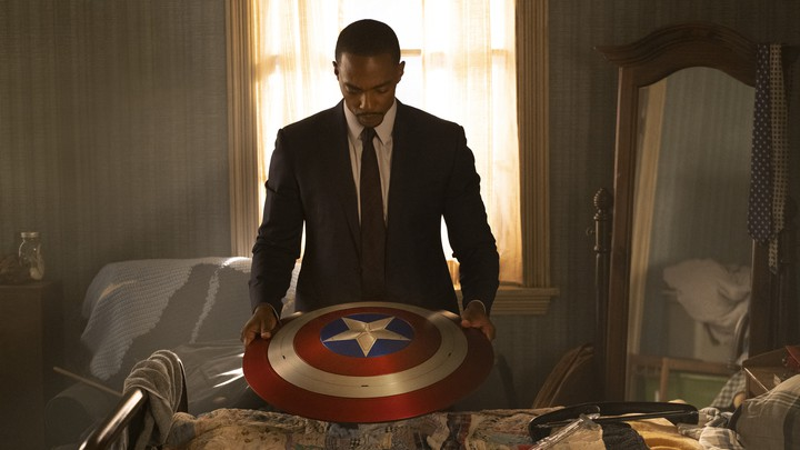 Sam Wilson (played by Anthony Mackie) looks down at Captain America's shield in his hands