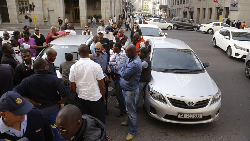 Uber taxi drivers in South Africa stand near their cars and block a road during a protest