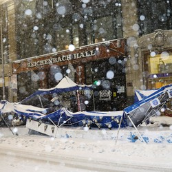 An outdoor dining tent is seen crumpled on the sidewalk during a snowstorm