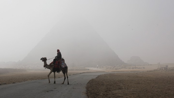A photograph of a person riding a camel