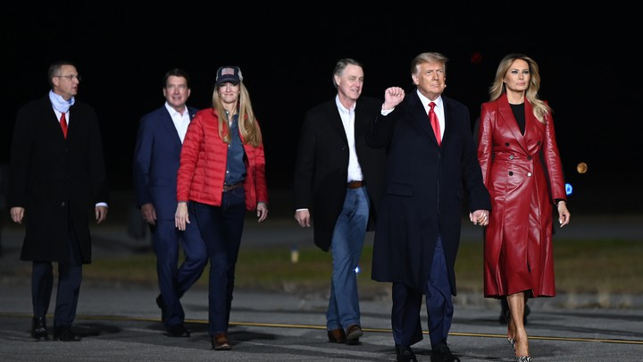 Donald Trump, Melania Trump, and the two Republican Senate candidates in Georgia walk with two others along an apparent tarmac. President Trump has his right fist raised.