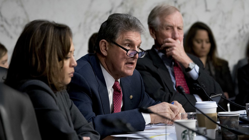 Senator Joe Manchin of West Virginia asks a question at a March 2018 Senate committee meeting. He is flanked by Senator Kamala Harris of California and Senator Angus King of Maine.