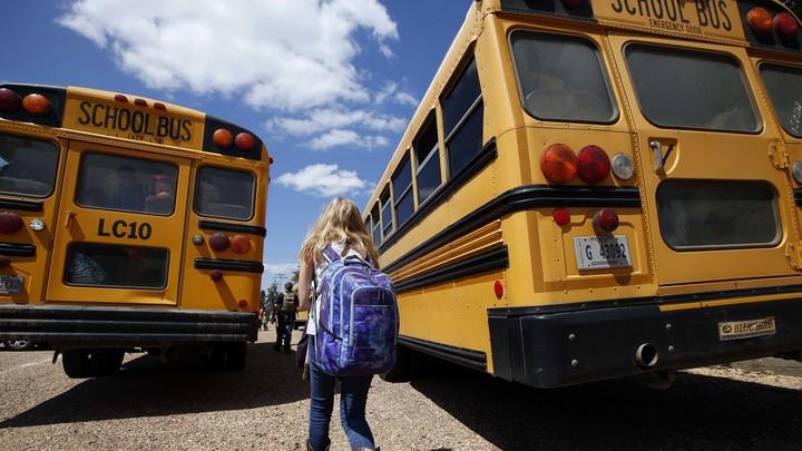 A girl walks toward two school buses.