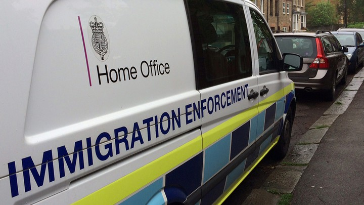 "A British government Home Office van is seen with the words ""immigration enforcement"" along its side."