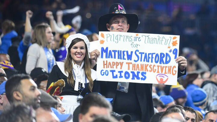 Fans holds signs during the game between the Detroit Lions and the Minnesota Vikings on Thanksgiving at Ford Field