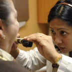 A female doctor in a white coat examines a patient