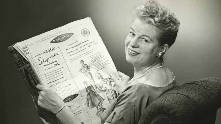 A black-and-white image of a woman reading a 1950s newspaper
