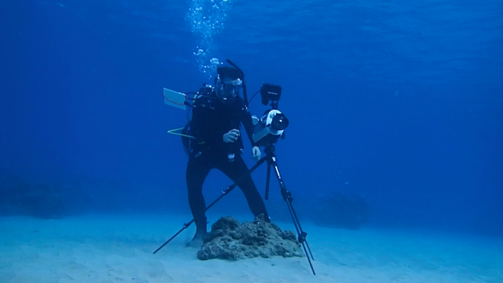 A diver wearing scuba equipment sets up a camera on a tripod underwater.