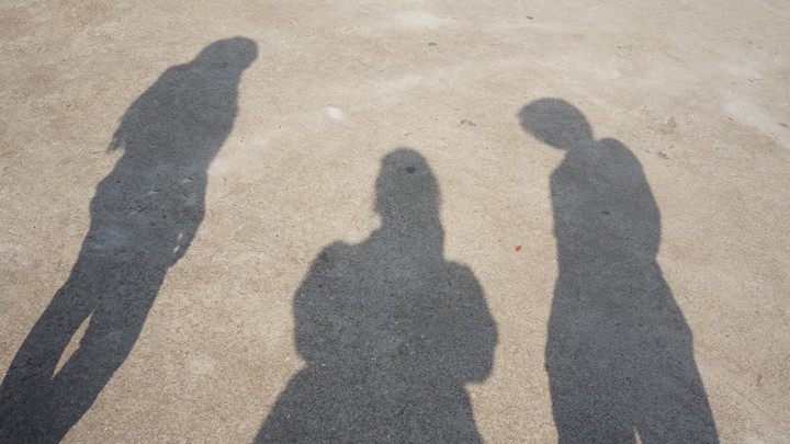 The shadows of three figures on the ground