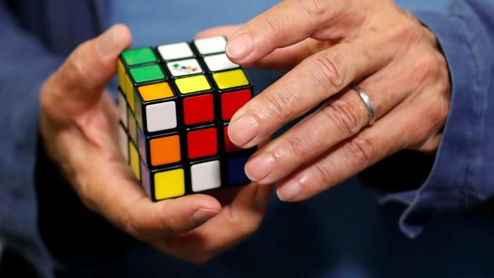A man holds a Rubik's cube