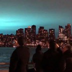 People take photos on their phones of the blue, lit-up sky over the New York City skyline.