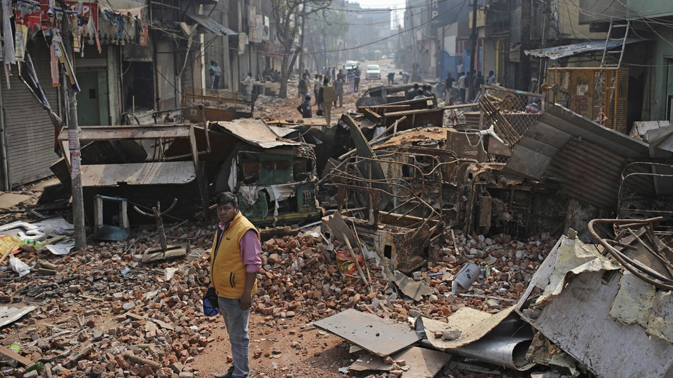 A Delhi municipal worker on a street vandalized in Tuesday's violence in New Delhi, India.