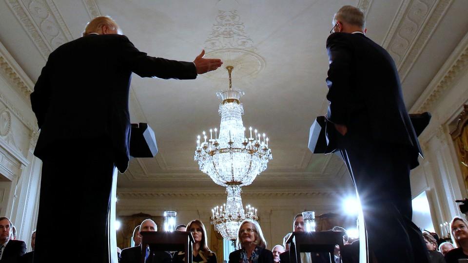 President Donald Trump gestures toward the former Australian prime minister inside the White House