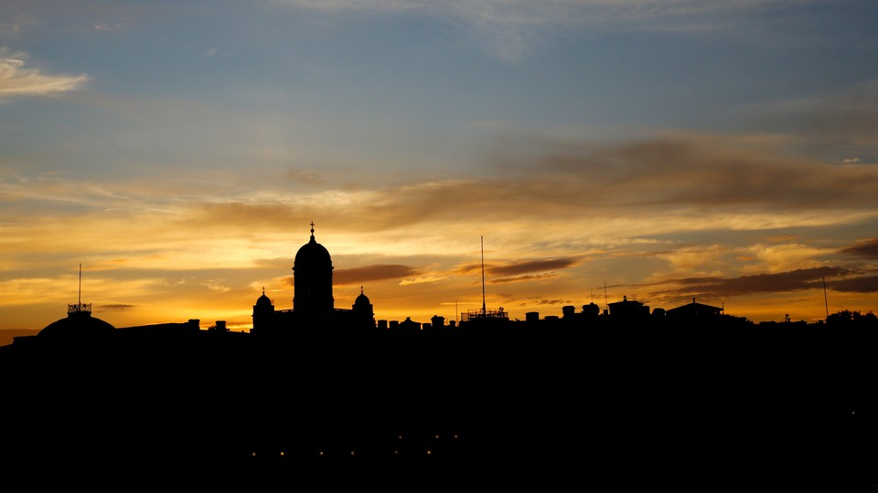 The sun sets behind the Presidential Palace and the cathedral in Helsinki.