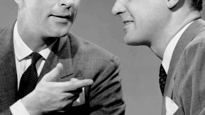 "A black and white close up of two men in suits talking; one points at the other in a ""you got it"" sort of gesture"