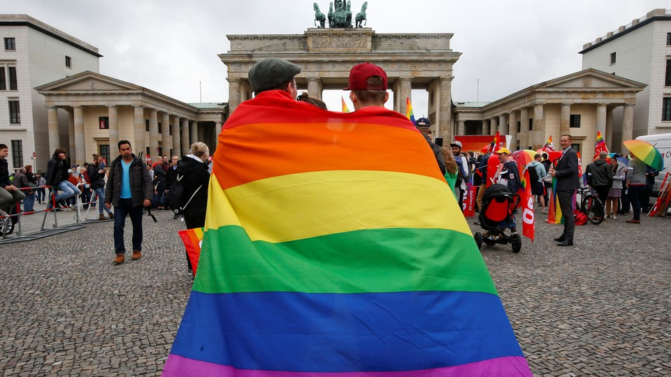People celebrate Germany's legalization of same-sex marriage in front of the Brandenburg Gate in Berlin on June 30, 2017.