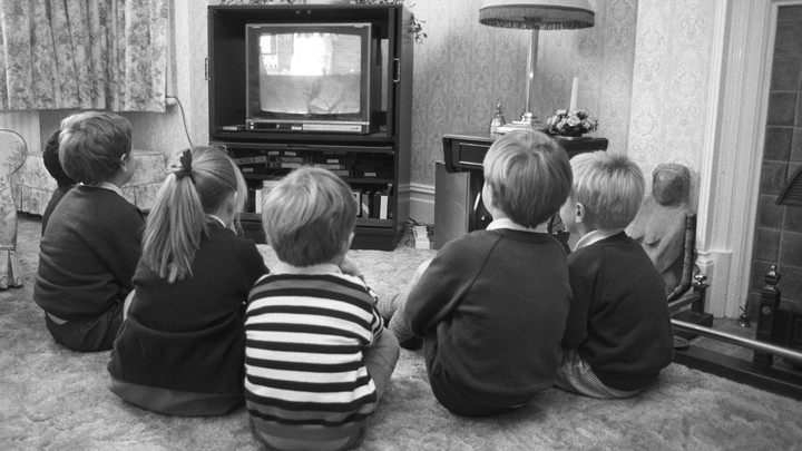 A black-and-white photo of children watching television