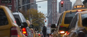 A policeman stands guard between a line of New York City yellow taxis and cabs.