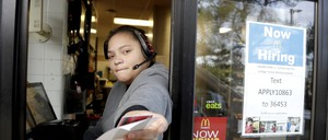 A woman works at a McDonald's drive-through window.
