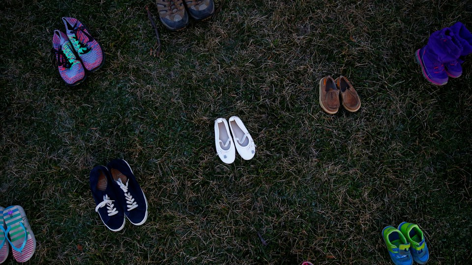 Pairs of shoes arranged in rows on grass