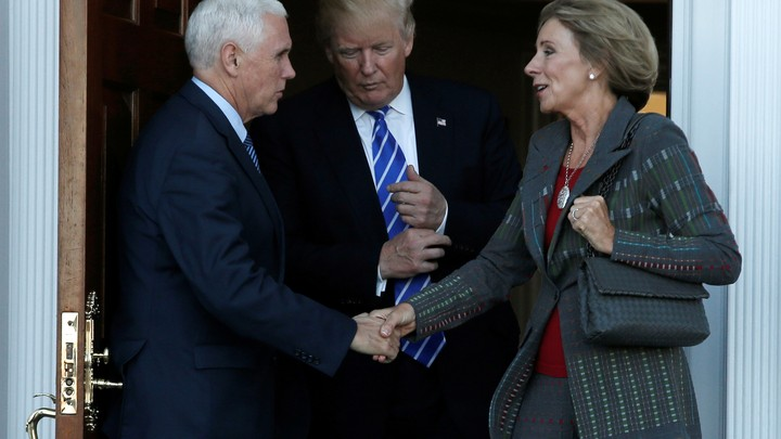Vice President-elect Mike Pence shakes Education Secretary Appointee Betsy DeVos's hand. President-elect Donald Trump stand between them.