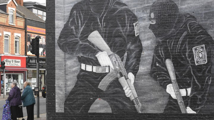 Pedestrians pass a political mural in Belfast, Northern Ireland, showing two men in balaclavas holding guns.