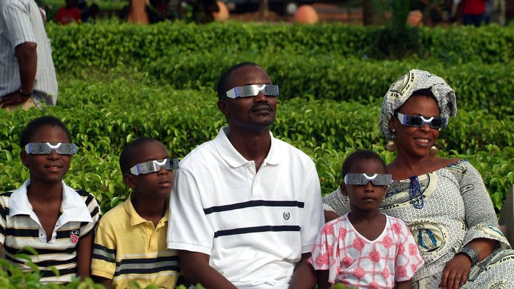 A family looks forward while wearing eclipse glasses.