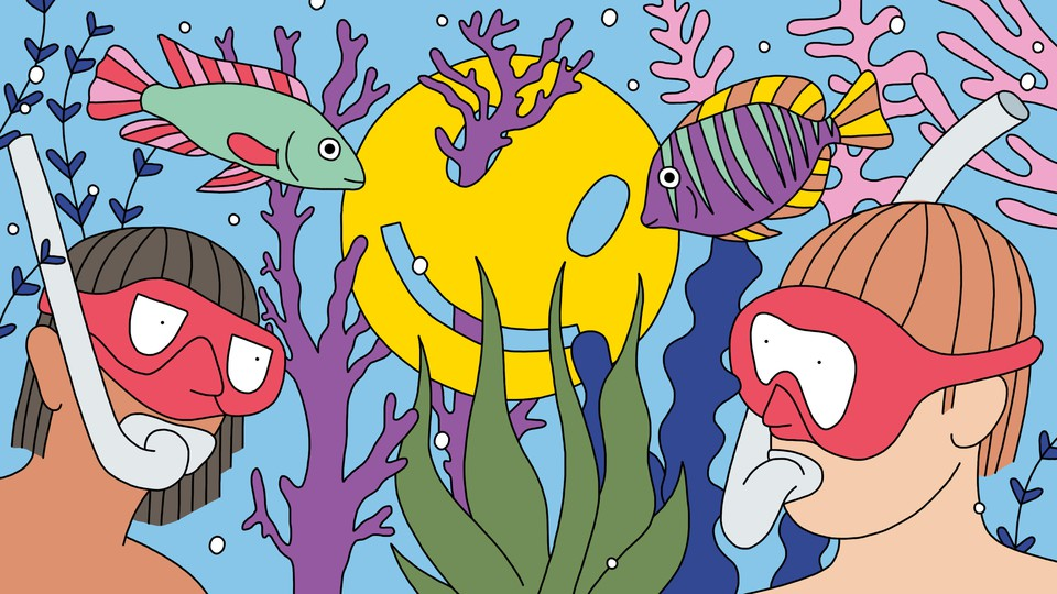 Two people snorkel on a colorful reef, where a smiley face is caught on a piece of coral