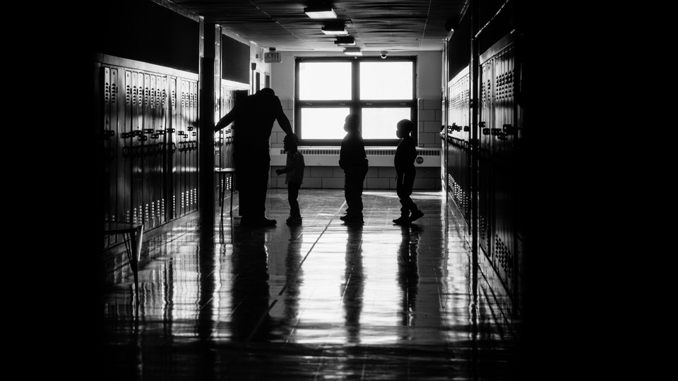 A black-and-white photograph of schoolchildren waiting in a hallway line to enter a classroom