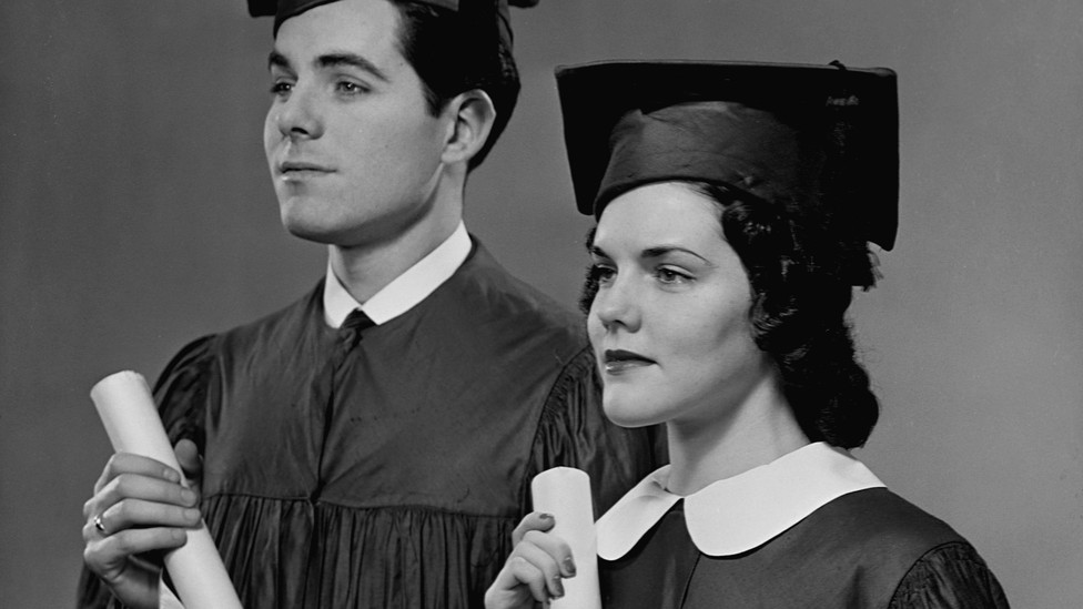 A man and a woman hold college diplomas