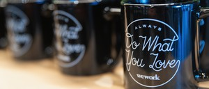 """WeWork-branded coffee mugs that say """"Always do what you love"""""""