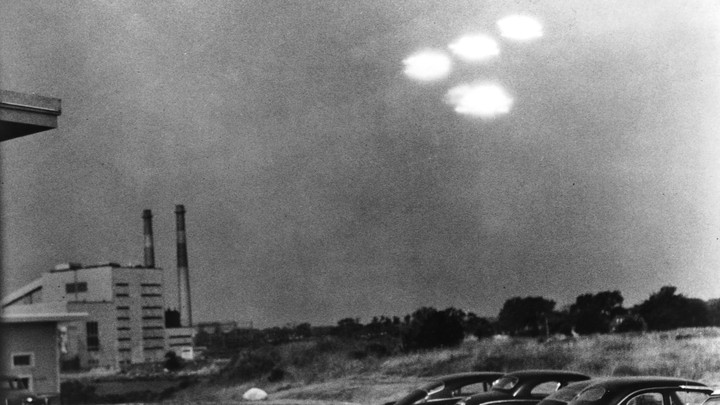 A cluster of glowing unidentified objects hovers in the sky over Salem, Massachusetts, in 1952.