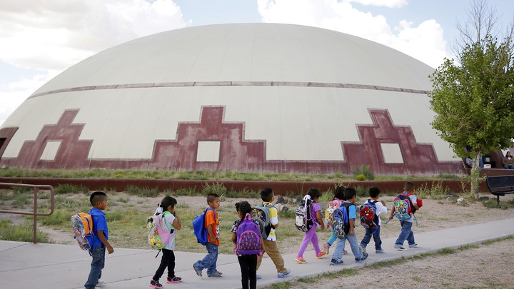 A group of children wearing backpacks walk past a building.
