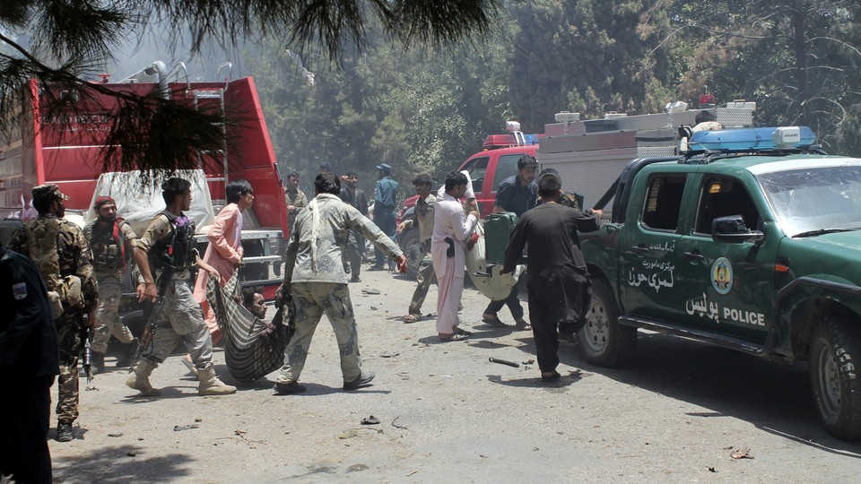 Afghans carry an injured man after a suicide car bombing in Helmand province on June 22, 2017.