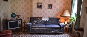 A living room with a plastic-wrapped sofa and patterned wallpaper