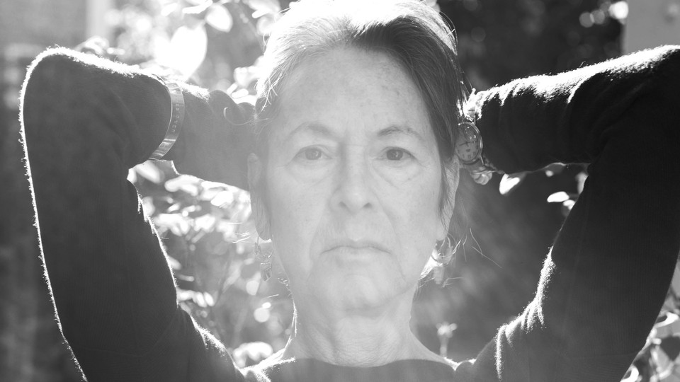 A black-and-white photo of Louise Glück in sunlight
