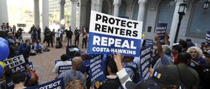 "A crowd with signs that say ""protect renters"" at a press conference."