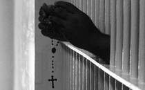An inmate's hands shown through bars, holding a rosary
