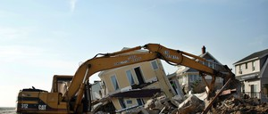 A crane in front of a destroyed house.
