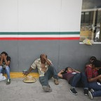 Asylum-seekers sit in Matamoros, Mexico, waiting to enter the U.S.